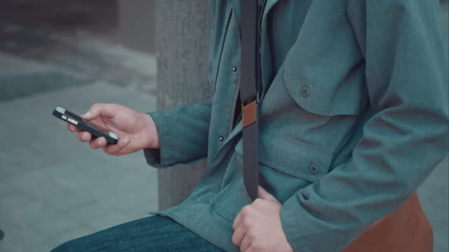 Man checking phone in urban setting video