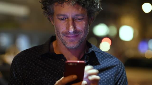 Man checking smartphone at night