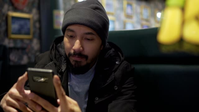 Man checking smartphone in cafe at night asian man checking and texting with smartphone at cafe minority groups stock videos & royalty-free footage