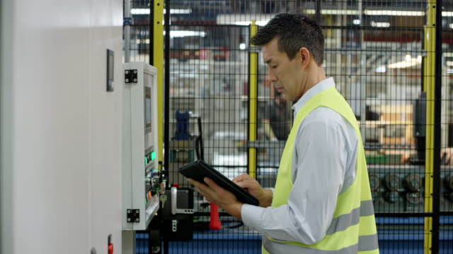 man kontrollera data på maskinens lcd-skärm i fabriken och jämföra den med data på tabletten - realtid bildbanksvideor och videomaterial från bakom kulisserna