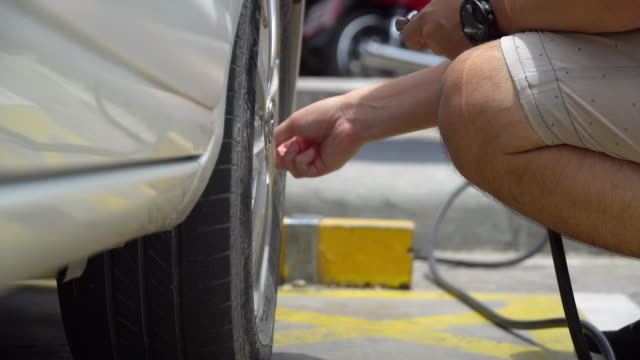 Man Checking tire pressure and filled air in tire.