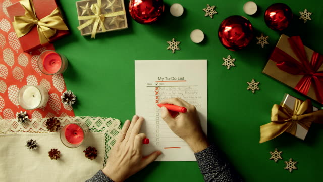 Man checks and fills up his duty to-do list on Christmas table with chroma key, top down shot video