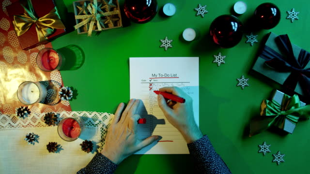 Man checks and fills up his duty to-do list on New Year table with chroma key, top down shot video