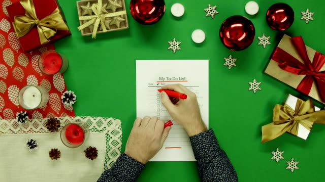 Man checks and fills up his duty to-do list on Xmas table with chroma key, top down shot video