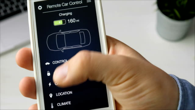 Man checks charge level of his car. Charging in progress Car remote control using smartphone application fictional interface. video