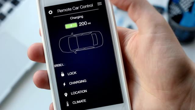 男は、彼の電気自動車の充電レベルをチェックします。バッテリーを充電します。車のリモコンがスマート フォン アプリケーション架空インターフェイスを使用します。 - 生態系点の映像素材/bロール