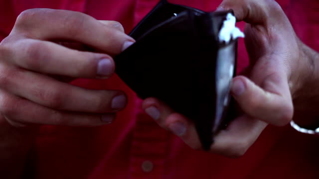 man checks his wallet and sees that he is broke or bankrupt - fare la lotta video stock e b–roll