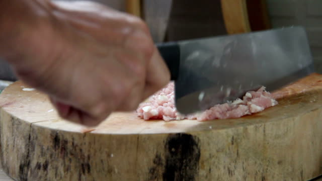 man chef cuts the pork on a cutting Board in kitchen video