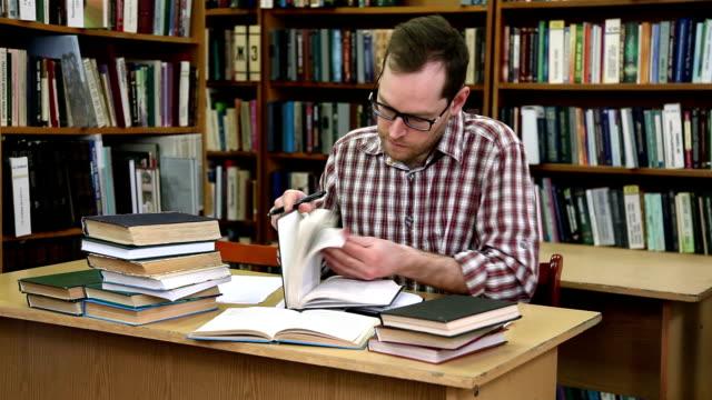 stockvideo's en b-roll-footage met man cheking boeken in de bibliotheek - literatuur