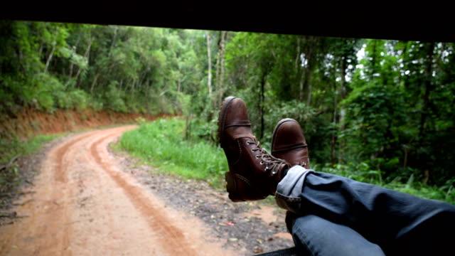 man chilling in the back of pickup truck on country road - dżinsy filmów i materiałów b-roll