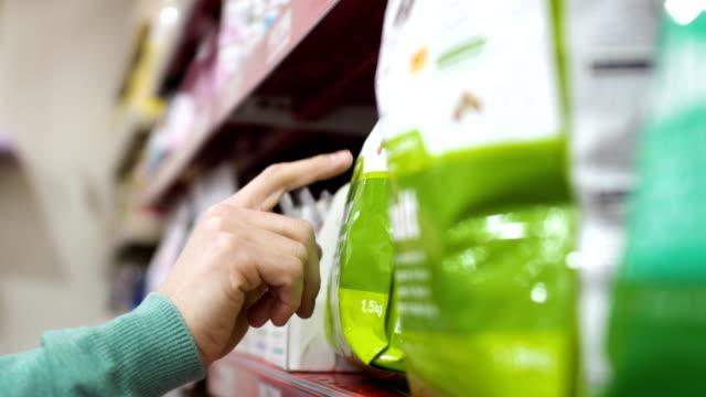 man choose feed for his dog in pet shop - prodotti supermercato video stock e b–roll