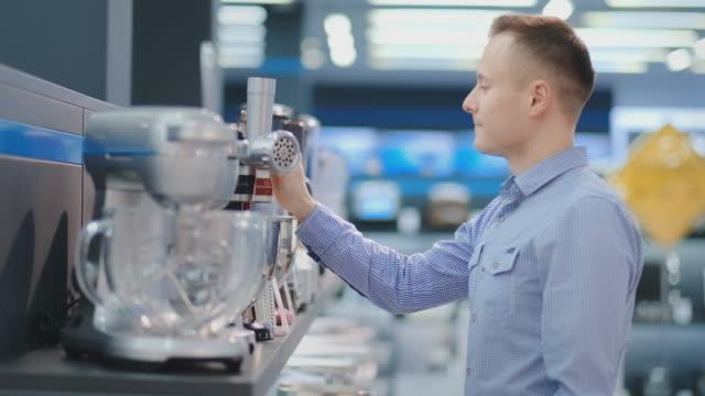 vidéos et rushes de un homme choisit un mélangeur dans les appareils électroménagers de cuisine de magasin dans ses mains et considère la conception et les caractéristiques - batteur électrique