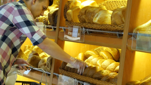 Man chooses a fresh bread loaf in the supermarket. Young guy taking a loaf of bread from the shelf and smelling it. Shopping in the grocery