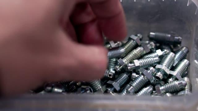 Man chooses metal parts and bolts Man chooses metal parts and bolts bolt fastener stock videos & royalty-free footage