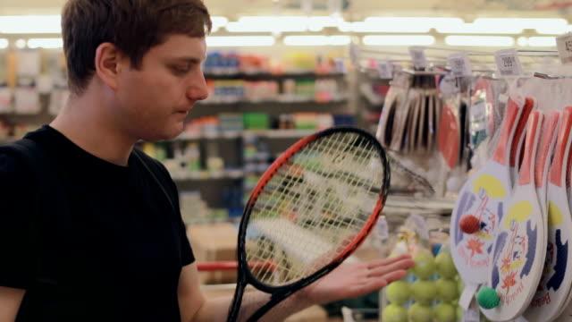 vídeos y material grabado en eventos de stock de hombre elige equipos deportivos en la tienda - bádminton deporte
