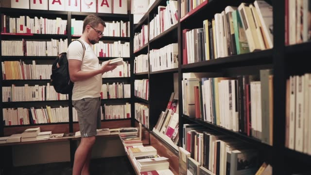 Man choosing a book in a store. Side view shot of a casual guy choosing new book in a bookstore. Man taking book from a shelf and read a little. textbook stock videos & royalty-free footage