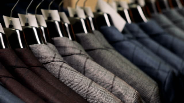 Man choosing a suit at tailor's shop Men's suit at tailor's shop. Men's hands choose a jacket in their wardrobe. Male choosing dress stock videos & royalty-free footage