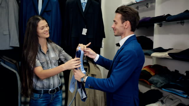 Man choosing a tie with a assistants help video