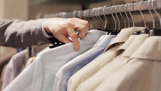 vídeos de stock e filmes b-roll de man choosing clothes on hanger in clothing store - escolher