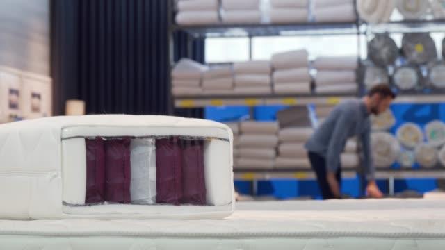 vídeos y material grabado en eventos de stock de hombre eligiendo cómoda cama ortopédica y colchón en la tienda de muebles - colchón
