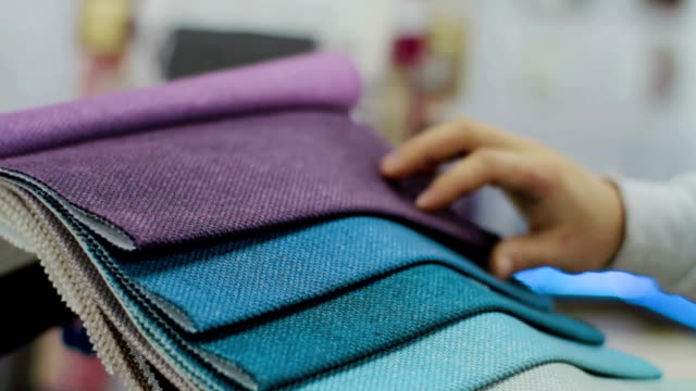 Man choosing Fabric Samples Of Different Colors for sofa - video