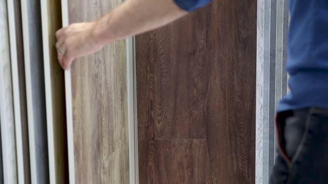 man väljer golv laminatdesign från prover för sin heminredning i golv butik - golv bildbanksvideor och videomaterial från bakom kulisserna