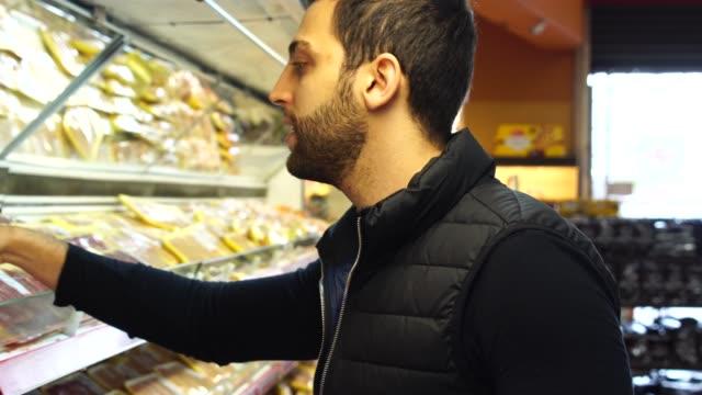 mann, die auswahl von produkten im supermarkt - wahlmöglichkeit stock-videos und b-roll-filmmaterial