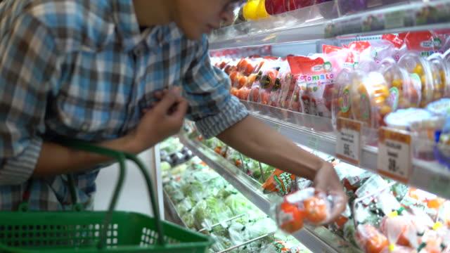 vídeos de stock, filmes e b-roll de homem, escolhendo os produtos no supermercado - estilo de vida dos abastados