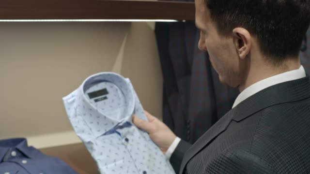 Man Choosing Stylish Shirt Zoom out shot of young man in suit choosing between two stylish shirts in menswear clothing store button down shirt stock videos & royalty-free footage