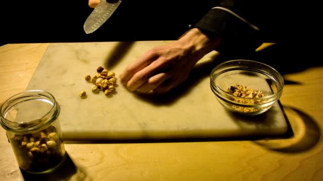 Man chopping hazelnut nuts. video