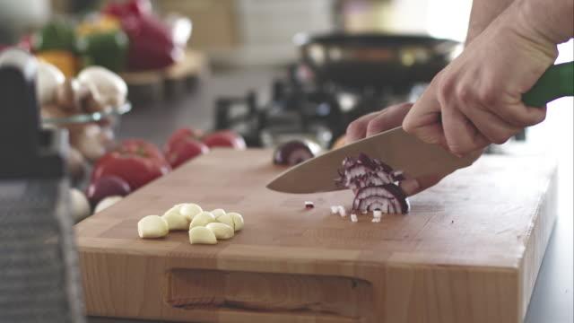 Man chopping red onion on cutting board video