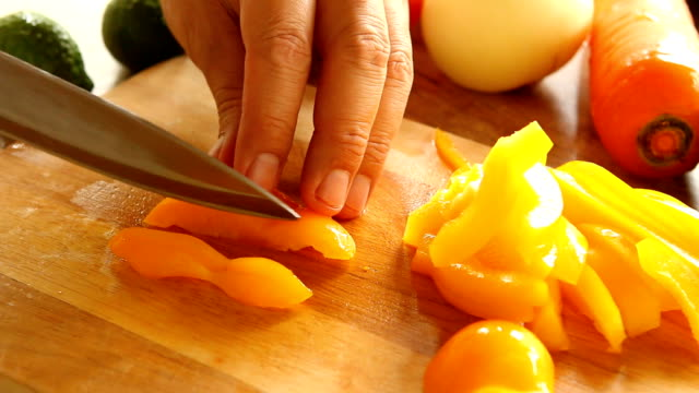 Man chopping sweet pepper on board