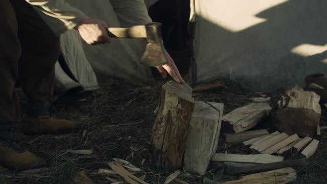 vídeos y material grabado en eventos de stock de hombre para picar de madera. vida de las personas civiles en la aldea. recreación medieval. - vikingo