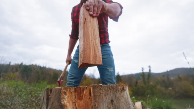SLO MO Man chopping wood with his axe outside