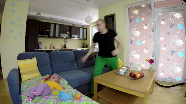 man clean floor with hoover and worried baby cry on sofa. video