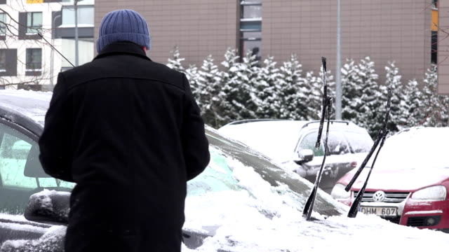 vidéos et rushes de neige propre d'homme du pare-brise de voiture après la chute de neige lourde. fullhd - raclette