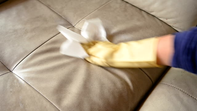 man cleaning a leather sofa with chemical foam - lucidare video stock e b–roll