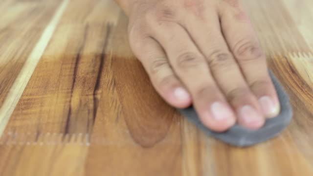 mann reinigung und polieren einer holzoberfläche und auftragen von holzpflegeprodukten. - wachs epilation stock-videos und b-roll-filmmaterial