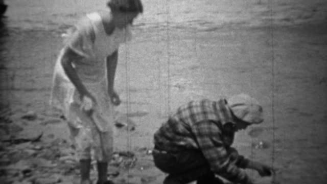 1935: Man cleaning fish creekside while wife brings frying pan. video
