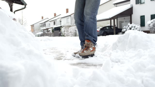 CLOSE UP: Man cleaning fresh snow from the driveway in idyllic suburbia video
