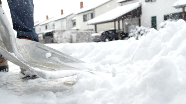 CLOSE UP: Man cleaning fresh snow in front of the house in idyllic suburban town video