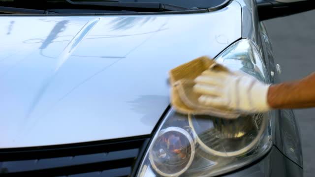 uomo che pulisce fari su auto, lavoro part-time per studenti, servizio autolavaggio - lucidare video stock e b–roll