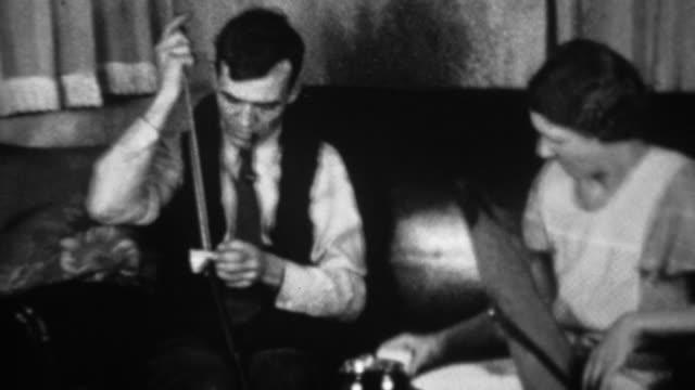 1936: mann reinigung waffe zu hause während unterstützende frau uhren. - editorial videos stock-videos und b-roll-filmmaterial