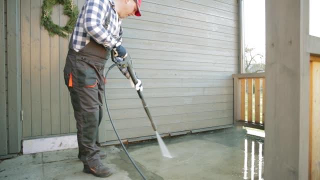 vídeos y material grabado en eventos de stock de hombre terraza de limpieza con un limpiador de alta presión de agua en la barandilla de la terraza de madera - fuerza