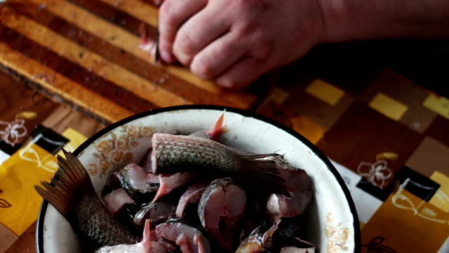 Man cleans and cuts fresh fish in the home kitchen video