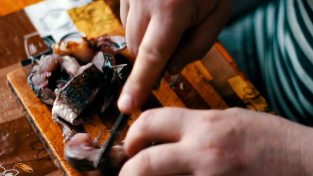 Man cleans and cuts fresh fish in the home kitchen. video