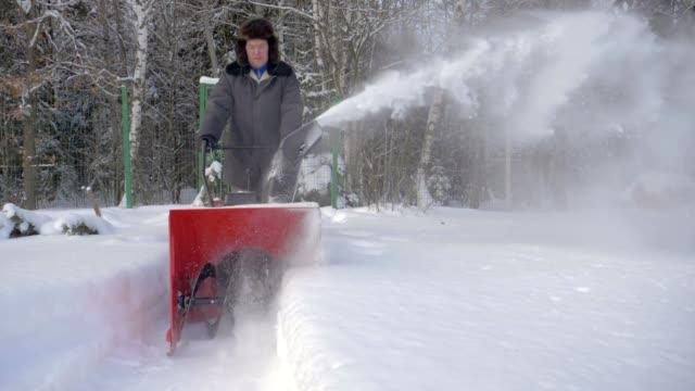 vídeos y material grabado en eventos de stock de hombre limpia la nieve con la máquina de remoción de nieve fondo el bosque en invierno - nieve amontonada