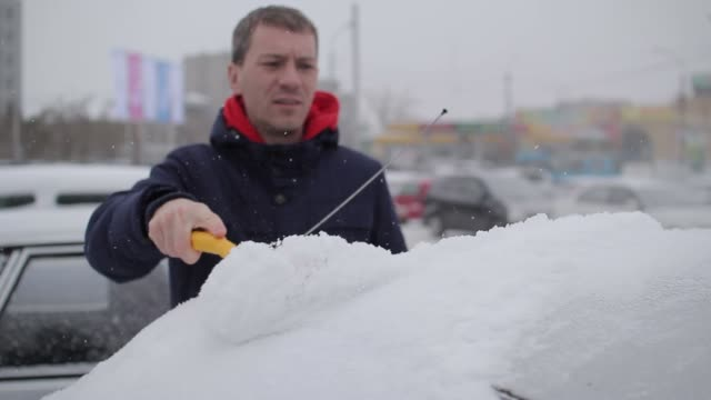 man cleans the car from snow with a brush video