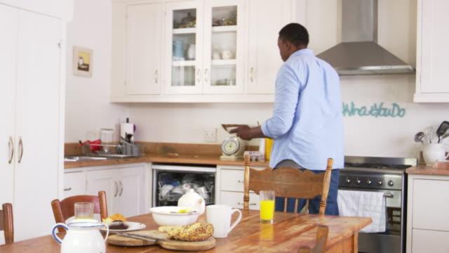 Hombre claro mesa de desayuno y carga del lavavajillas - vídeo