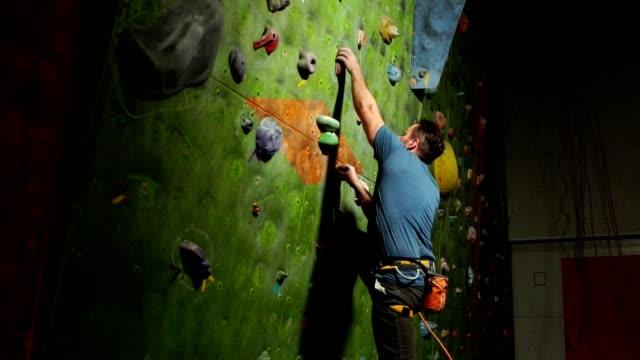 ein mann bergsteiger beginnt an der wand das felsmassiv mit den versicherungen in den felsen hinauf zu klettern. profisportler - bouldering stock-videos und b-roll-filmmaterial